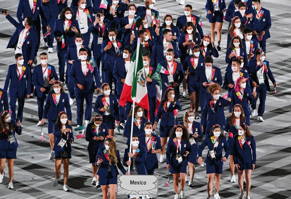Gabriela López y Rommel Pacheco ondearon la bandera de México en el desfile de las delegaciones de todo el mundo. Foto: Martin Bureau / AFP